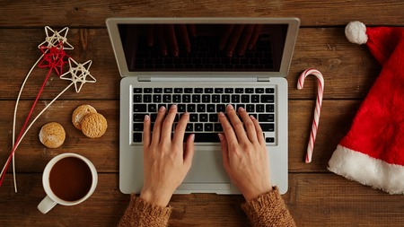 female christmas: Female hands typing on laptop with Christmas stuffs around