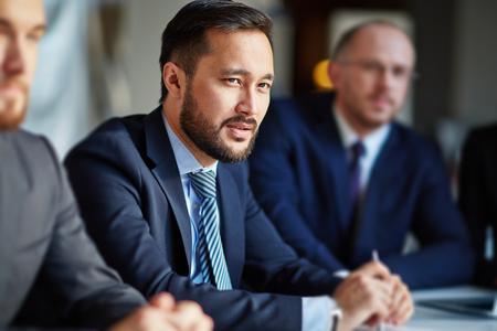 liderazgo: Apuesto hombre de negocios sentado en una reunión Foto de archivo