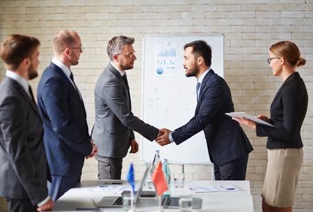 saludo de manos: Los socios comerciales Apret�n de manos de un acuerdo en la oficina