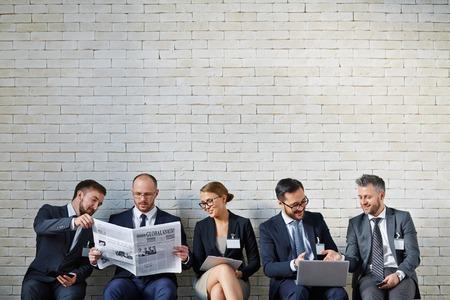 periodicos: La gente de negocios de espera en una cola