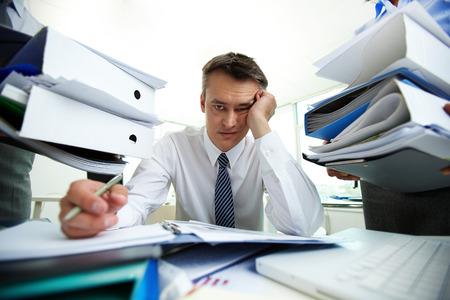 agotado: El encargado cansado tiene muchos papeles en la oficina