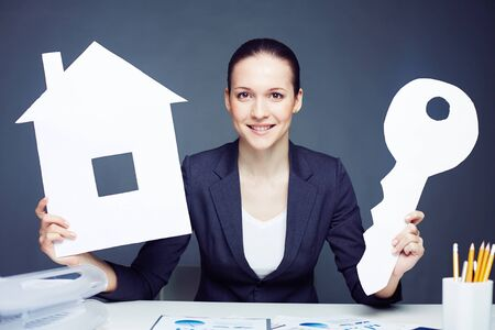 business loans: Smiling businesswoman holding figure of home and key Stock Photo