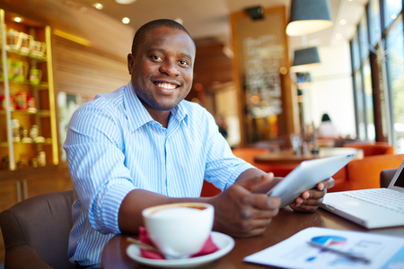 african business: Happy businessman with touchpad drinking coffee at cafe