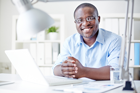 african business man: Smiling businessman sitting at his table at office