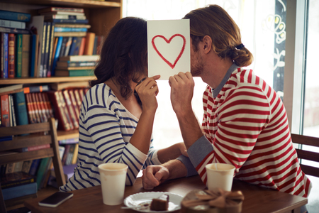 Young couple hiding behind the paper with red heart