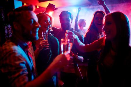 jovenes tomando alcohol: Grupo de j�venes celebrando con bebidas en la discoteca Foto de archivo