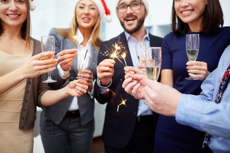 holiday gathering: Joyful colleagues with champagne and Bengal lights enjoying Christmas party