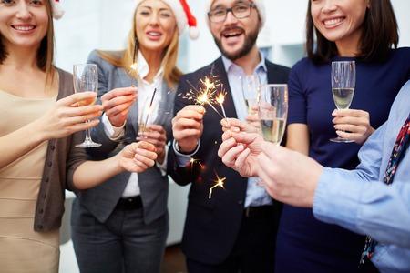 Joyful Kollegen mit Champagner und bengalische Feuer genießen Weihnachtsfeier Standard-Bild