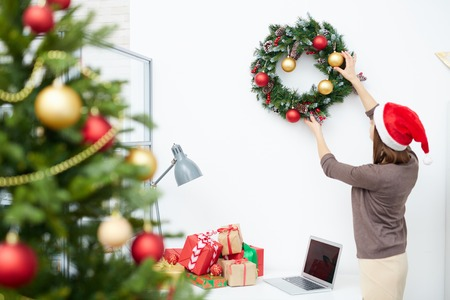 Businesswoman in Santa cap hanging Christmas wreath over workplace in office