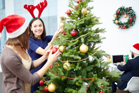 business christmas: Two businesswomen decorating Christmas tree in office Stock Photo