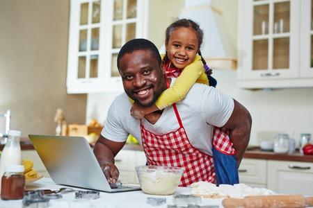 persona alegre: Hombre joven busca de la receta en la red con la hija en la espalda Foto de archivo