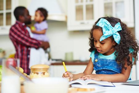 colegiala: Colegiala linda que hace notas en el ejercicio libro en casa