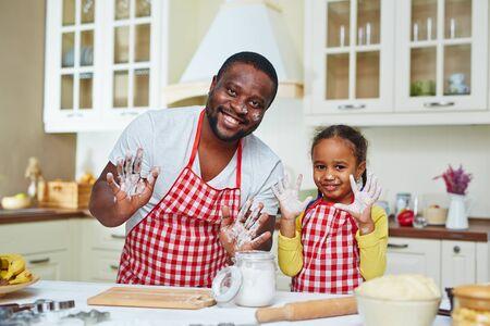 familias jovenes: Hombre joven feliz y su hija que muestran sus palmas con harina