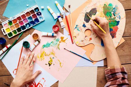 gouache: Artist hands painting with gouache