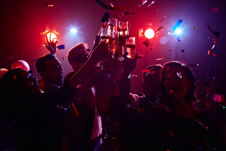 cheers: Young friendly people toasting in night club Stock Photo