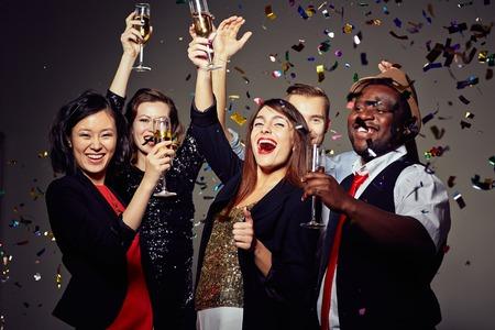personas reunidas: Gente alegre brindando con champán en la fiesta Foto de archivo
