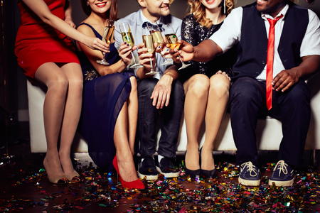 Grupo de amigos que tintinean con champán Foto de archivo