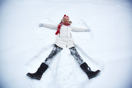 snowdrift: Happy young woman in winter-wear lying in snowdrift