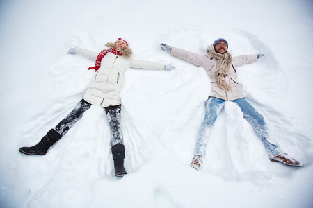 snowdrift: Happy couple in winter-wear lying in snowdrift