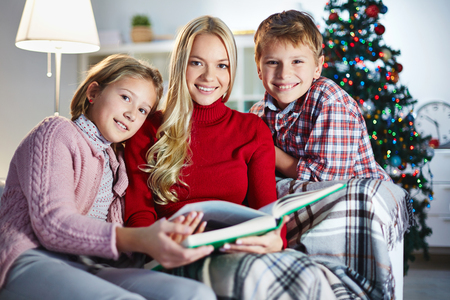 Family of three reading book on Christmas evening photo