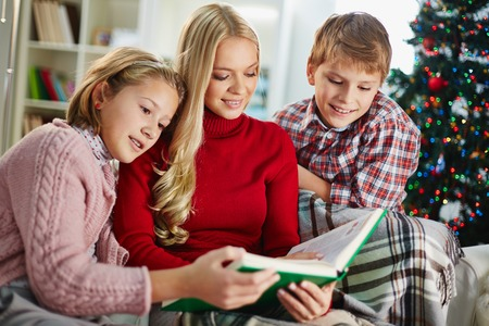 Woman and two kids reading at home on Christmas evening photo
