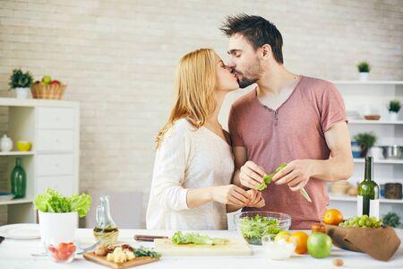 novios besandose: Pareja joven y cariñoso que besa mientras se cocina la ensalada Foto de archivo