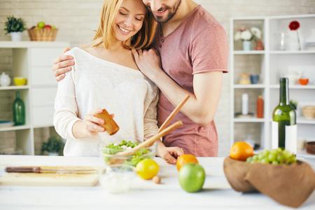 adding: Happy couple adding salt into fresh salad Stock Photo