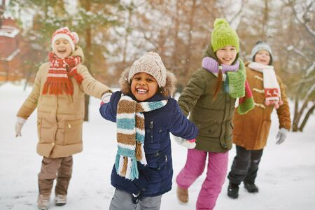 winterwear: Cheerful girl looking at camera with her friends on background Stock Photo