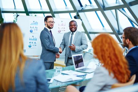 Aziatische en Afrikaanse zakenlieden handshaking en op zoek naar medewerkers in het kantoor