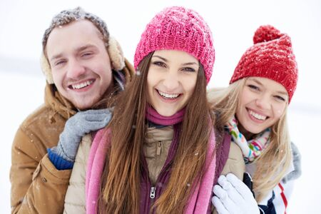 winterwear: Joyful friends in winterwear looking at camera with smiles outdoors Stock Photo