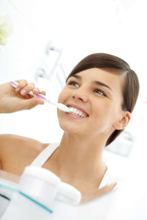 woman mirror: Young woman cleaning her teeth before mirror