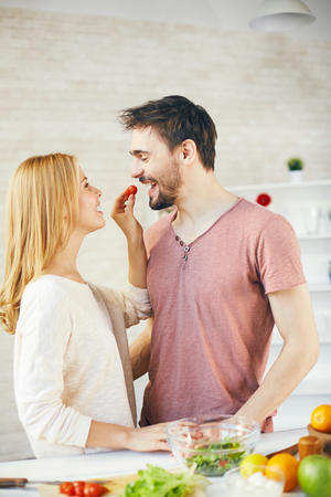 eating salad: Happy young woman giving red tomato to her husband