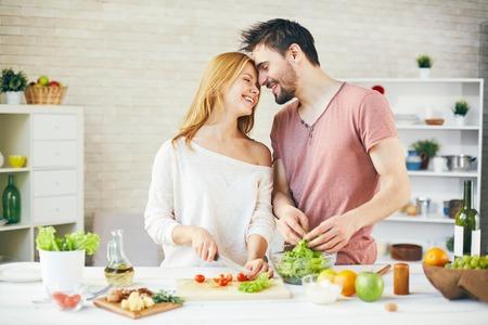 mujeres cocinando: Joven pareja de cocinar ensalada vegetariana fresca juntos Foto de archivo