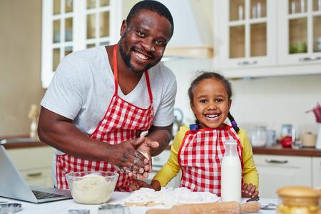 padre e hija: Hombre afroamericano y niña cocinar repostería casera juntos