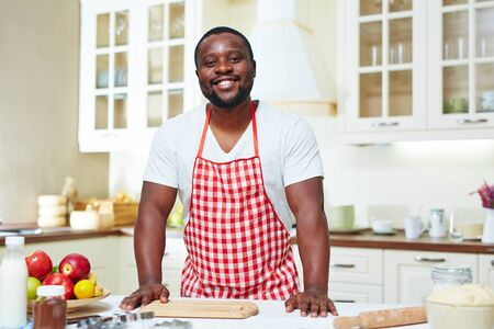 rollingpin: Happy young man in apron looking at camera in the kitchen Stock Photo