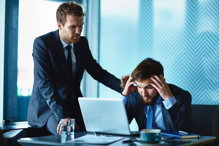 colleagues: Young businessman reassuring his frustrated colleague Stock Photo