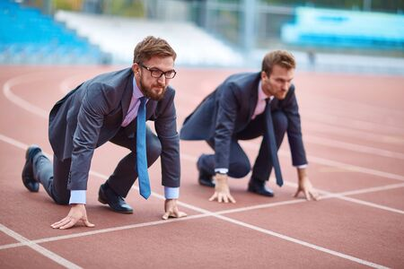 competitors: Two businessmen standing at start on stadium track Stock Photo