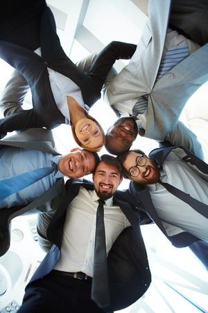 personas de pie: Hombres de negocios sonrientes jóvenes de pie abrazando