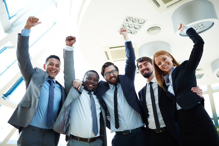 business team: Business team with arms raised and smiling