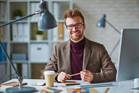 Glimlachend jonge zakenman zit op zijn werkplek en glimlachen Stockfoto