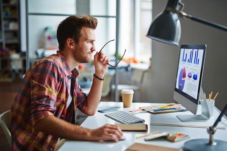 Az ember, mint a tervező ül az asztalnál, és dolgozik a számítógépen