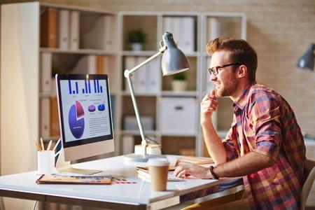 Jonge executive werken met grafieken op zijn computer Stockfoto