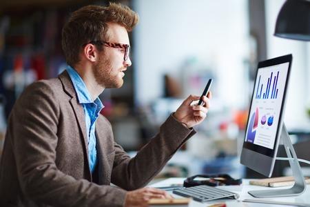 usando computadora: Hombre de negocios serio que usa el ordenador y trabajar con tablas en la oficina