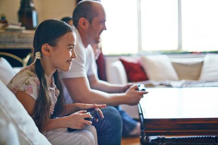 niños jugando videojuegos: Muchacha sonriente jugando juegos de video con su padre