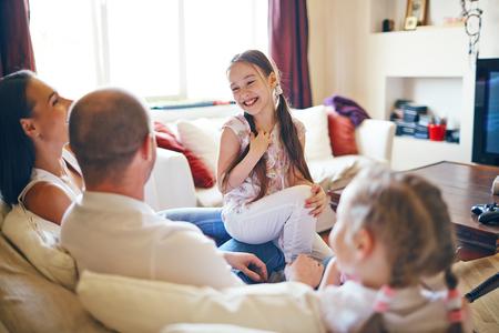 reir: Linda chica sentada junto a su familia y riendo en casa