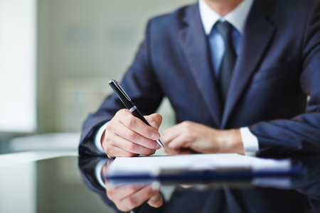 writing on paper: Businessman sitting at office desk and signing a contract Stock Photo