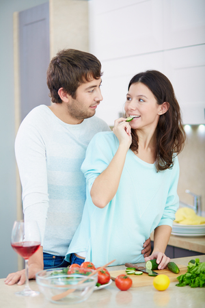 young wife: Young husband and wife cooking salad together Stock Photo