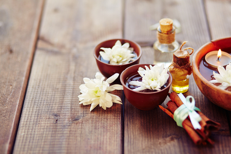 bath essence: Bowls with flowers, bunch of cinnamon and aromatic oils in spa salon