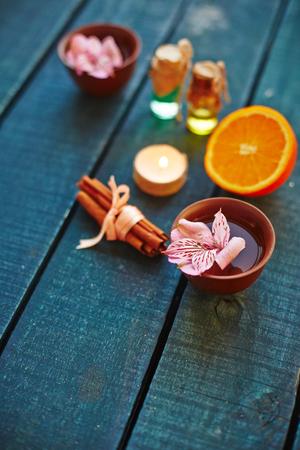 bath essence: Lotus flower, cinnamon, orange, oils and burning candle on wooden table