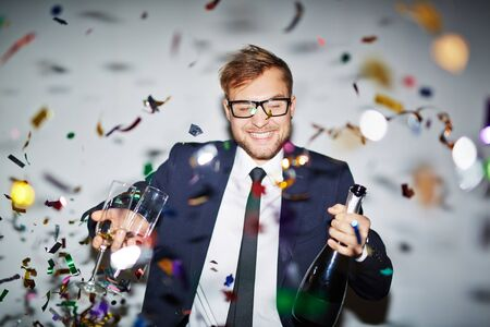 occasion: Happy businessman with bottle of champagne and two glasses standing under falling confetti Stock Photo